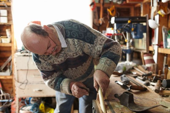 Older man carving at a workbench