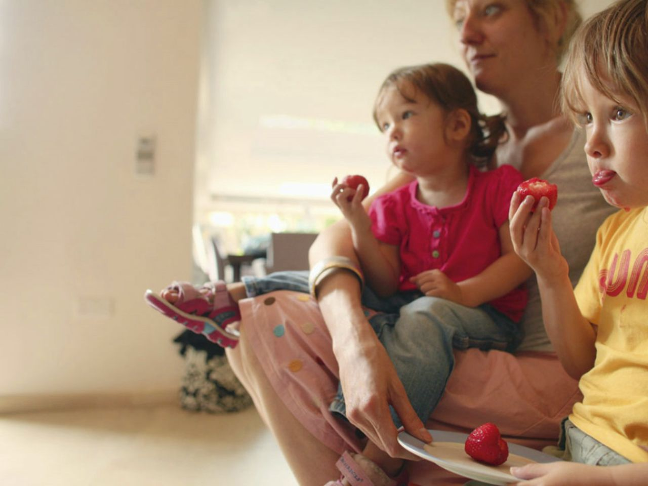 An image showing a family eating strawberries