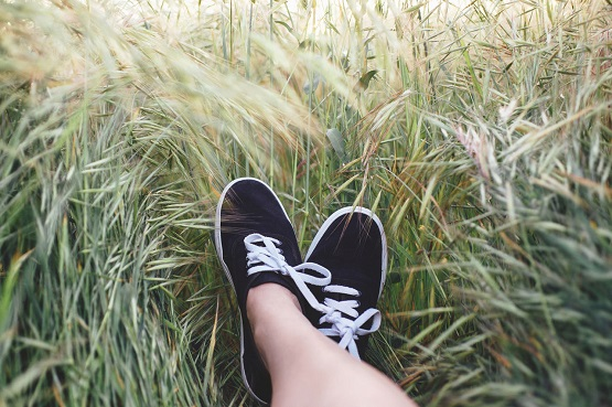 A photograph taken from the point of view of a woman sitting down in long grass, looking across to her crossed feet