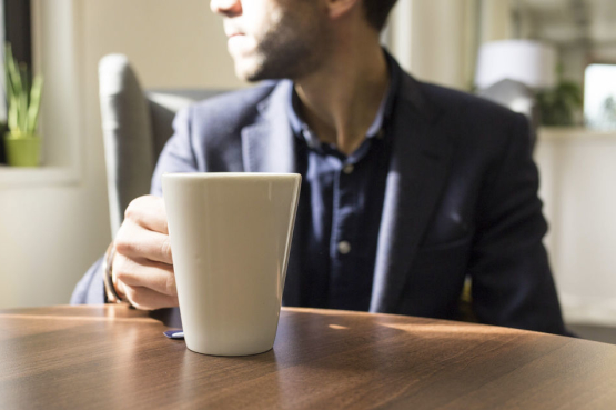 Image of man drinking tea and looking out of the window