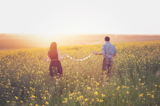 Couple walking in a field of flowers