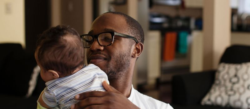 Image of a man holding his baby