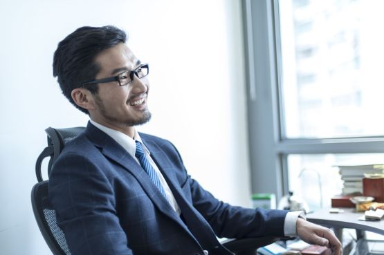 Businessman sitting in his office smiling