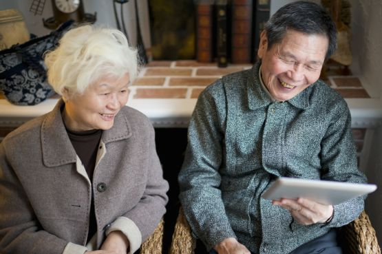 An image of an older couple looking at a tablet device