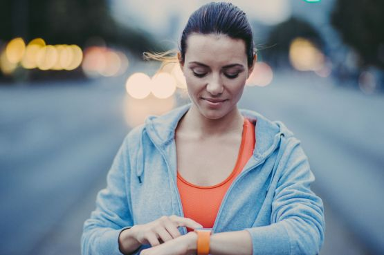 A female runner sets her watch