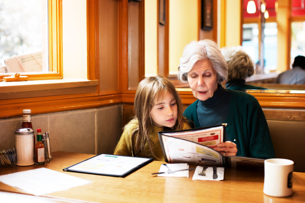 Older lady and young girl sitting in a restaurant